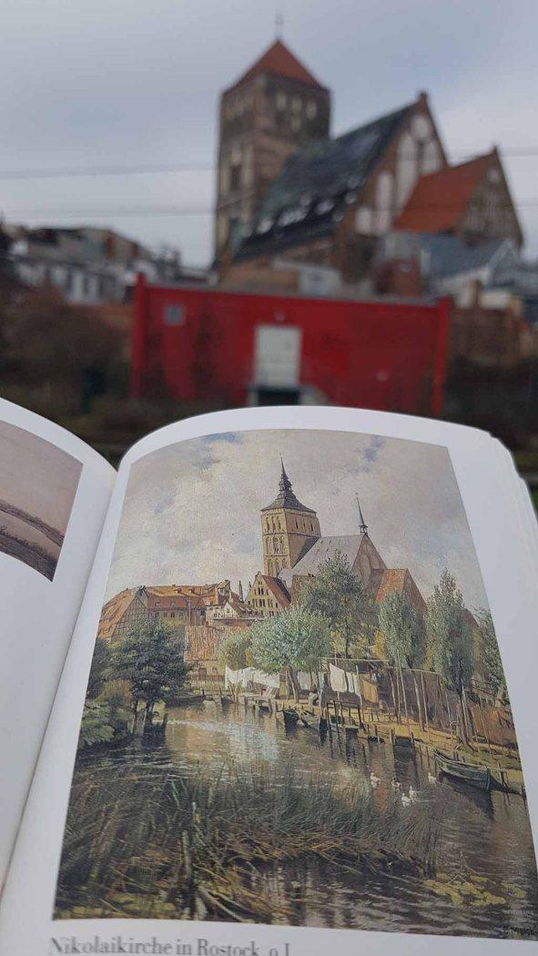 Stadtansicht Rostocks mit St. Nikolai und ein Blick in das Buch - Carl Malchin - Ein mecklenburgischer Maler - von Lisa Jürß